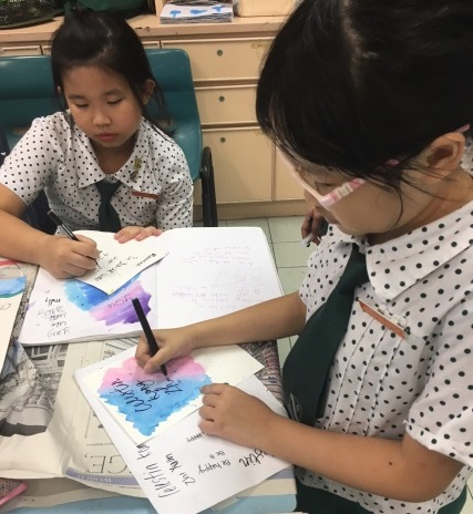 Practising their calligraphy skills during the P6 Leaders Workshop 2.jpg